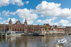 Canal cruise boat in front of Amsterdam central railway station stock photos