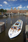 Canal cruise boat in front of amsterdam central railway station Stock Photo