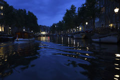 A canal cruise boat makes waves in an Amsterdam canal at night. A cruise boat leaves a shining blue wake in an Amsterdam canal during an evening cruise Royalty Free Stock Image