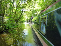 Canal narrowboats passing under trees Royalty Free Stock Photography