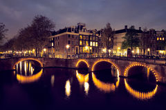 Canal d'Amterdam, pont et maisons médiévales le soir Images stock