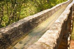 Canal d'irrigation avec de vieux éléments en pierre en nature photos stock