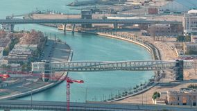 Canal da água de Dubai com o passadiço durante o timelapse aéreo do por do sol do telhado do centro dos arranha-céus filme