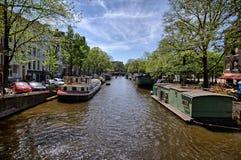 Canal de Amsterdão Cruzar através da cidade é um destaque para turistas fotos de stock