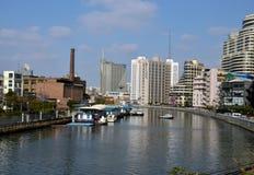 Canal de rivière avec la cheminée et les édifices hauts de service Changhaï Chine de bateau Photographie stock