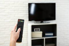 Canal de televisão em mudança da mulher com controlo a distância na sala de visitas, foco disponível imagem de stock royalty free
