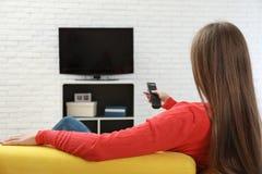 Canal de televisão em mudança da mulher com controlo a distância no sofá imagem de stock royalty free