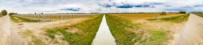 canal divides harvested land  and plowed land with precast piles Royalty Free Stock Images