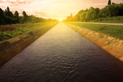 Canal do nascer do sol e da irrigação na estação das chuvas Foto de Stock Royalty Free