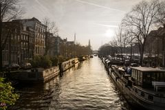 Canal en Amsterdam con puesta del sol en el fondo imagenes de archivo