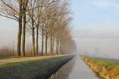 Canal en el campo cerca de un camino de la grava y una fila de árboles Imagenes de archivo