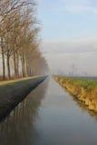 Canal en el campo cerca de un camino de la grava y una fila de árboles Fotografía de archivo