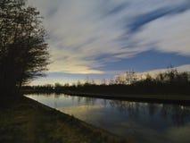 Canal en la exposición larga de las nubes móviles del cielo azul de la noche imágenes de archivo libres de regalías