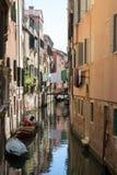 Canal estrecho en Venecia con las góndolas y las fachadas amarradas de casas viejas foto de archivo
