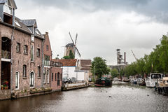 Canal of Gouda with vessels and windmill a cloudy day. stock photo
