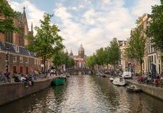 Canal holandês famoso e construções velhas tradicionais no distrito claro vermelho de Amsterdão foto de stock
