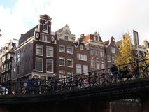 Canal houses in Amsterdam, Netherlands. Canal houses taken from a low point of view combined with a bridge and bicycles Royalty Free Stock Images