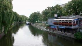 Canal idílico de Landwehrkanal en Berlín, Kreuzberg con un café, los barcos y los cisnes en el verano metrajes