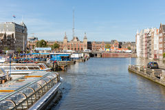 Canal with landing stage of cruise ships downtown in Amsterdam Royalty Free Stock Photo