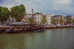 Canal large avec l'immeuble de brique à côté de lui et d'un bon nombre de bateaux amarrés dans un jour nuageux chez Dordrecht photo libre de droits