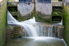Canal lock cill with water spilling through gate Stock Photos