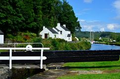 Canal lock gate. Crinan canal lock gate landscape with tress, gate keepers house and boats stock photos