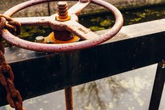 Canal Lock vintage wheel water flow control. Vintage and historic canal lock wheel opens the water overflow while the leaves float along the water Stock Photo