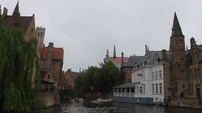 Canal, medieval architecture and boats in Bruges stock footage