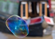 Large misshapen bubble in front of canal boat. Canal narrow boat with large soap bubble in fun and colorful image Stock Images