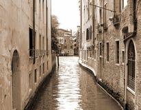 Canal navegável estreito em Veneza no sepia de Itália Imagem de Stock