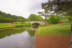 Canal at Norfolk Botanical Gardens. Stone Bridge over the canal at the Norfolk Virginia Botanical Gardens. Flowers emphasize the canal and bridge Royalty Free Stock Photo