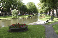 A canal and park bench along a canal in Edam, Netherlands. A park bench and flower box along a tree-lined canal in Edam, Netherlands Stock Images