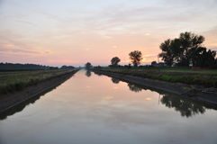 Canal in the Po plain by sunset, Lombardy, Italy Royalty Free Stock Photo