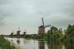 Canal recto con los arbustos y los molinoes de viento altos en el banco en un día nublado en Kinderdijk Imágenes de archivo libres de regalías