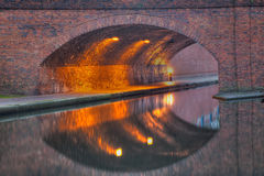 Canal Reflection with perfect symetry. A canal reflection showing a walkway and old brick arch at dusk Stock Photos