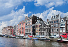 Canal with row of stately ancient mansions with moored boats, Amsterdam, Netherlands. Canal with row of stately ancient mansions with parked cars and moored stock images