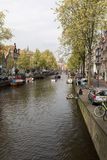 Canal  scene with a bicycles, boats and traditional Dutch houses in Red Light District. Amsterdam. Amsterdam, Netherlands - April 20, 2017: Canal  scene with a royalty free stock photos