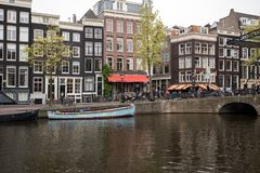 Canal scene with a bicycles, boats and traditional Dutch houses in Red Light District. Amsterdam. Amsterdam, Netherlands - April 20, 2017: Canal scene with a royalty free stock image