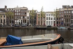 Canal scene with a bicycles, boats and traditional Dutch houses in Red Light District. Amsterdam. Netherlands. Amsterdam, Netherlands - April 20, 2017: Canal royalty free stock photography