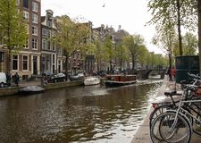 Canal  scene with a bicycles, boats and traditional Dutch houses in Red Light District. Amsterdam. Netherlands. Amsterdam, Netherlands - April 20, 2017: Canal stock images