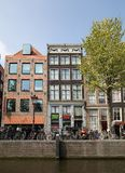 Canal  scene with a bicycles, sidewalk cafe and traditional Dutch houses in Amsterdam. Netherlands. Amsterdam, Netherlands - April 20, 2017: Canal  scene with a stock photo