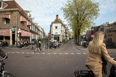 Canal scene with a bicycles, sidewalk cafe and traditional Dutch houses in Amsterdam. Amsterdam, Netherlands - April 20, 2017: Canal scene with a bicycles stock photos