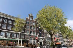 Canal scene with a bicycles, sidewalk cafe and traditional Dutch houses in Amsterdam. Netherlands. Amsterdam, Netherlands - April 20, 2017: Canal scene with a royalty free stock image