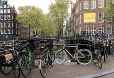 Canal scene with a bicycles and traditional Dutch houses in Red Light District. Amsterdam. Netherlands. Amsterdam, Netherlands - April 20, 2017: Canal scene with royalty free stock photo