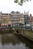 Canal  scene with a bicycles and traditional Dutch houses in Red Light District. Amsterdam. Netherlands. Amsterdam, Netherlands - April 20, 2017: Canal  scene stock photography