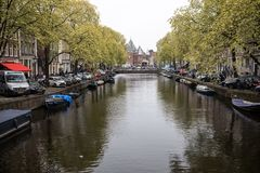 Canal scene with a boats and traditional Dutch houses in Red Light District. Amsterdam. Netherlands. Amsterdam, Netherlands - April 20, 2017: Canal scene with a stock photo