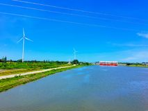 The irrigation canal has wind turbine used to generate electricity. Canal with a sea barrage, when the sea is higher, it will not flow back to the fresh water Royalty Free Stock Photos