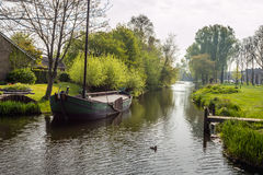 Canal with ship in a small Dutch village Stock Photos