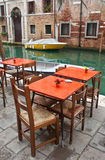 Canal side cafe, Venice, Italy. Orange tables at edge of small canal, Venice, Italy Stock Photo