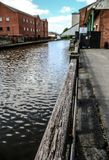 Canal Side in the centre of Wigan. Looking along a wooden barrier on the canal in Wigan Royalty Free Stock Photography
